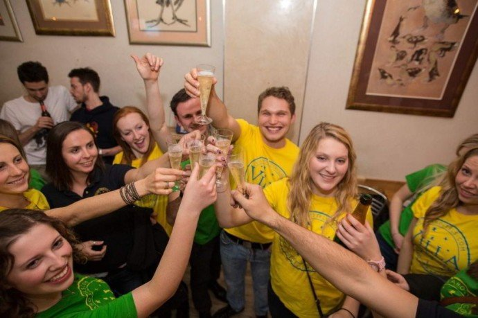 Staff in Yellow logo t-shirts raising a glass of champagne, Hostel Life with Villa Hostels