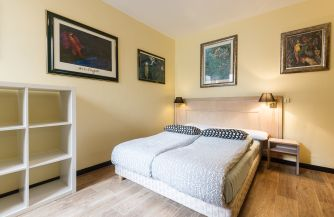 A nice room with a large comfortable bed and pictures on the walls and bedside lamps