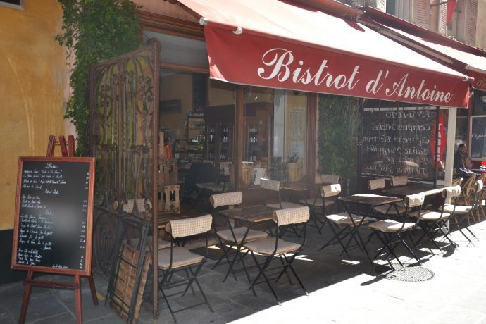 Outside seating under the red canopy of Bistrot Antoine, a great place to eat in Nice