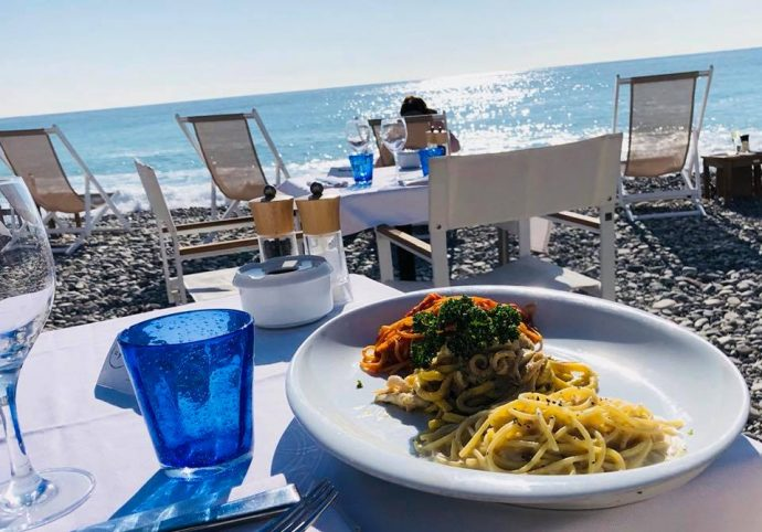 plate with pasta on a table in front of the beach
