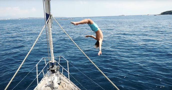 A person diving off of a boat into a calm blue sea