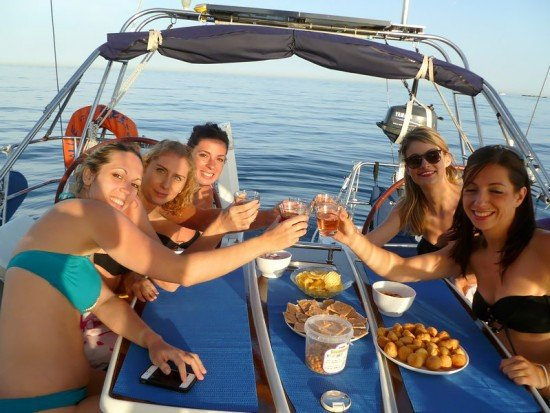 Friends cheering and having lunch on a boat on the French Riviera