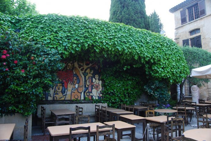 A restaurant terrace with tables and plants climbing the walls in St. Paul de Vence