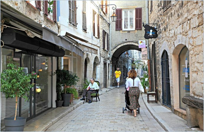 A old paved street in St Paul de Vence with a woman walking among the shops and art stores