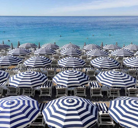 Rows of blue and white beach umbrellas in front of a turquoise sea