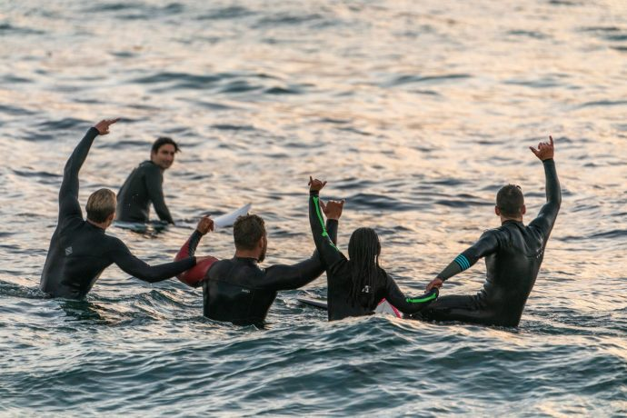A group of surfers sitting on their boards in the water