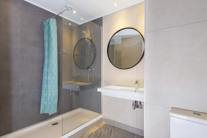 New bathroom with walk in shower, sink and large mirror, hostel in Nice, France