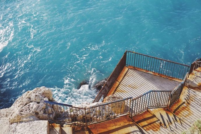 Some stairs heading down to a blue sea with a jumping off point