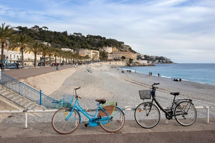 A quiet pebble beach on a sunny day with bicycles in the foreground and a beautiful blue sea