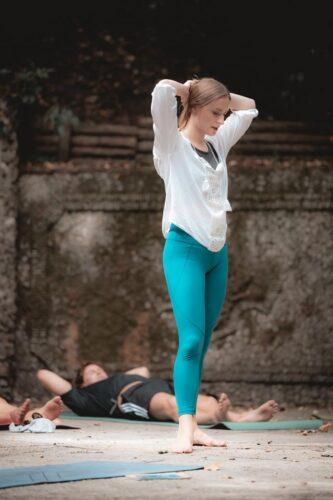 A yoga instructor in blue leggings teaching in Nice, France